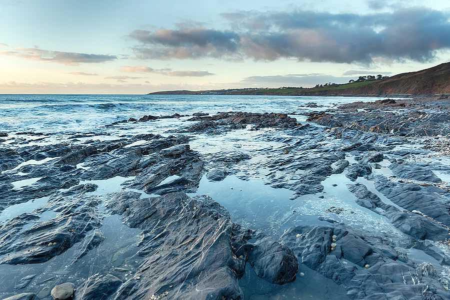 Rock pools at low tide on Pendower Beach in Cornwall